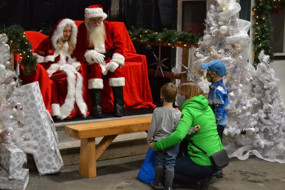 Mandy Moran who lives near Didsbury and children Grayson and Owen visit with Santa and Mrs. Claus during Olds Winter Wonderland on Nov. 22.  Doug Collie/MVP Staff