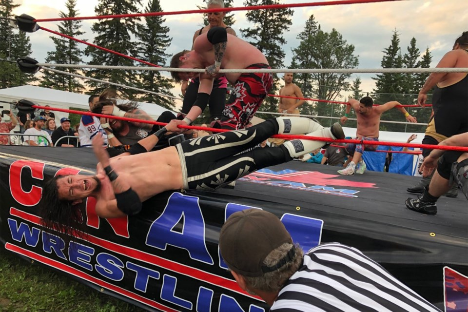 Wrestlers battle in the ring with hundreds of fans taking in the open-air action of the professional Can-Am Wrestling Resurrection at the Elkton Valley Campground on Saturday evening, July 3.  Photo courtesy of Helen Jackson
