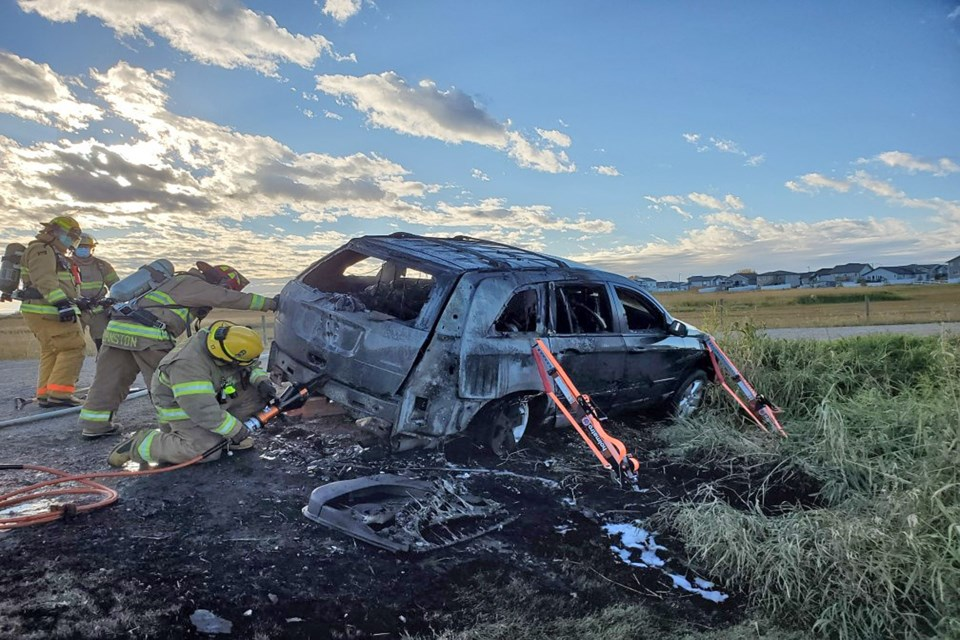 Penhold firefighters at work putting out a vehicle fire late Tuesday afternoon (Sept. 29) on Waskasoo Avenue. Submitted photo