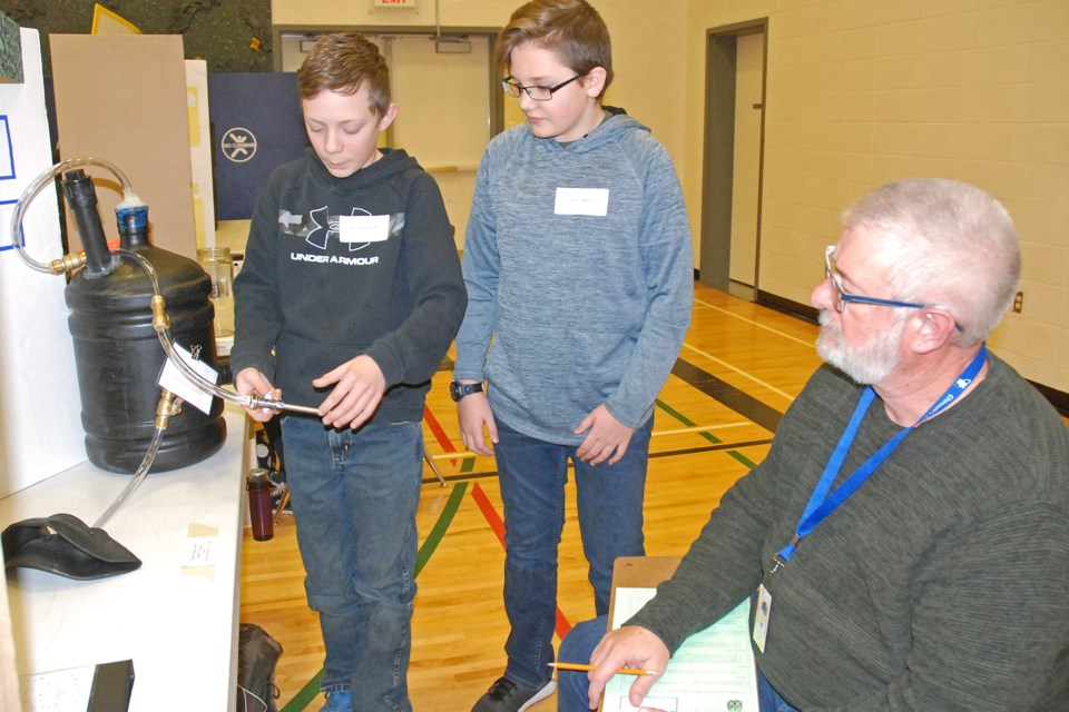 River Valley School science fair judge Mike Kapiczowski listens on Thursday, Jan. 30 as Grade 7 students Austin Fuchko, left, and Austin Nixon explain how they used an airtight anaerobic digester to determine whether manure or compost had a higher potential to create energy.  Simon Ducatel/MVP Staff