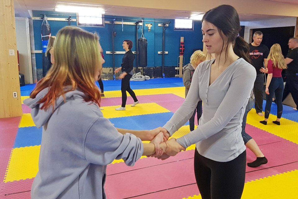 Sundre High School Grade 12 student and Leo club member Carmen Wolfe, right, practise how to break free from a wristlock with classmate Justice Dach during Youth Empowerment Day.