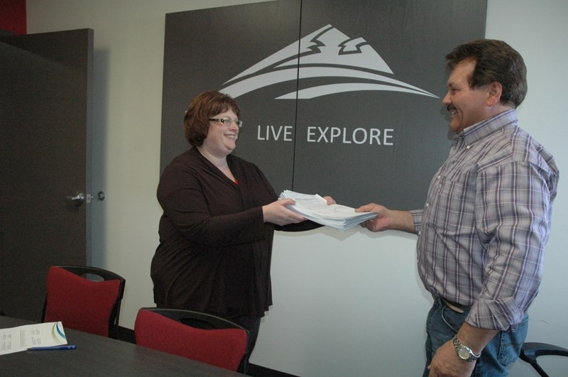 Rick Scown presents a petition to interim CAO Wanda Watson Neufeld last Friday which is signed by east side Sundre residents opposed to what they call the high cost of the