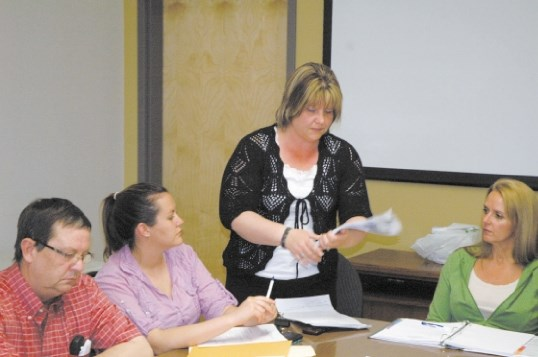 Monica St. Dennis, centre, hands out copies of a new business survey questionnaire during last week's chamber meeting.