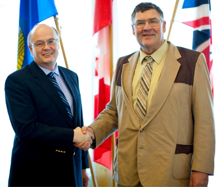 Newly minted county CAO Tony Martens receives congratulations from Reeve Paddy Munro.