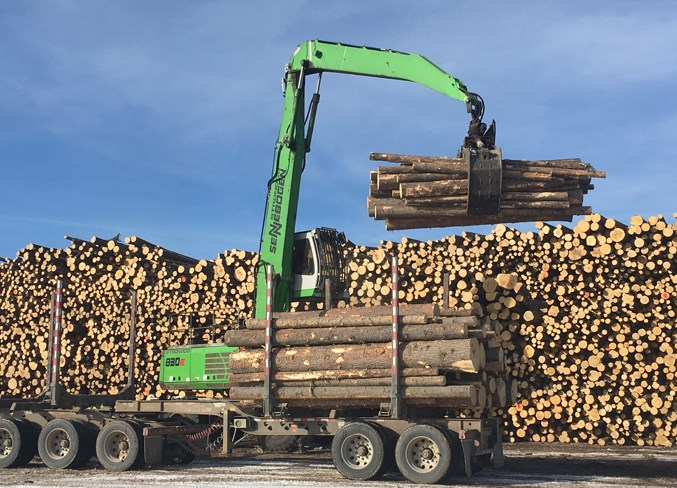 A crane operator unloads and stacks trees at Sundre Forest Products.