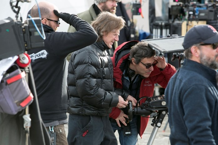 Camera operator Carey Toner, middle left, and director Paulo Barzman, middle right, view the scene through a remote monitor connected to a video camera.