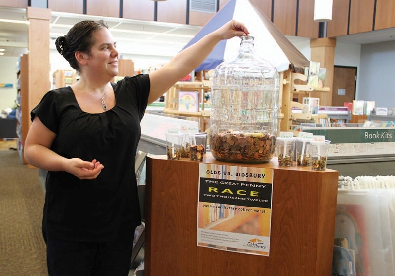 Olds library manager Lesley Winfield drops pennies into the carboy at the library.