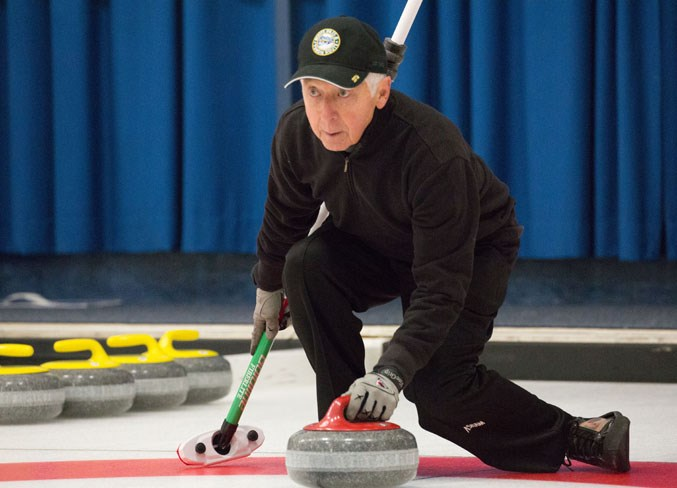 Grant Spence throws a rock at the curling club.