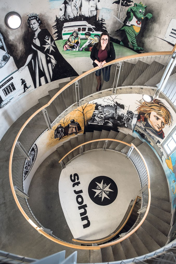 Meagan Taylor, office administrator of the St. John Ambulance Alberta Council, in a spiral stairwell depicting the history of the St. John Ambulance at their facility in Edmonton February 13, 2019.