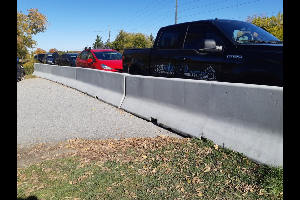 Vehicles are parked along Bathurst Street next to the cement barriers cutting off access to the Jokers Hill hiking trail parking lot. Supplied photo/Lisa Heckbert
