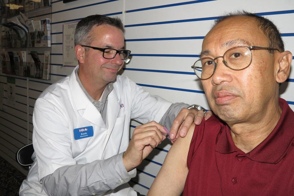 Photographer Greg King stoically receives his flu shot from pharmacist Kevin Dupuis of Robins Pharmacy on Main Street.  Photography by Greg King