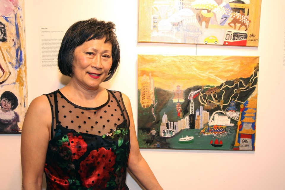 At the opening reception for the Mindful Project's Roots|Routes exhibit yesterday, artist Fanny Anderson stands by the triptych that tells the story of her family's journey from China.  Greg King for NewmarketToday