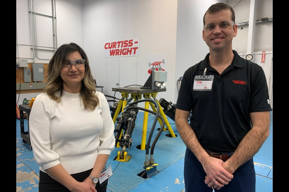Curtiss-Wright engineers Fareshta Hashemi (left) and Michael Nanowski stand before the shake table in the seismic test lab. Debora Kelly/NewmarketToday