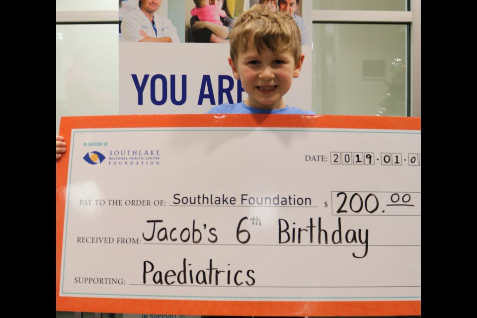 Six-year-old Jacob presents Southlake Regional Health Centre Foundation with $200, his birthday gift. Supplied photo/Southlake Foundation