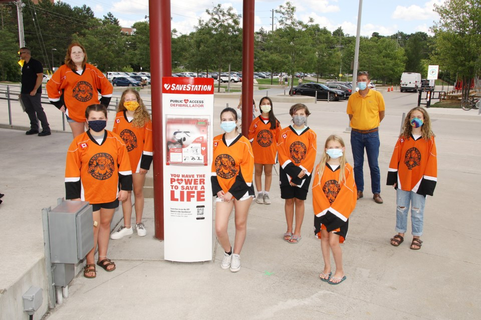 Members of the CYGHA Peewee Orange Crush team and Newmarket Mayor John Taylor at the unveiling of the SaveStation AED tower at Riverwalk Commons July 29.  Greg King for NewmarketToday