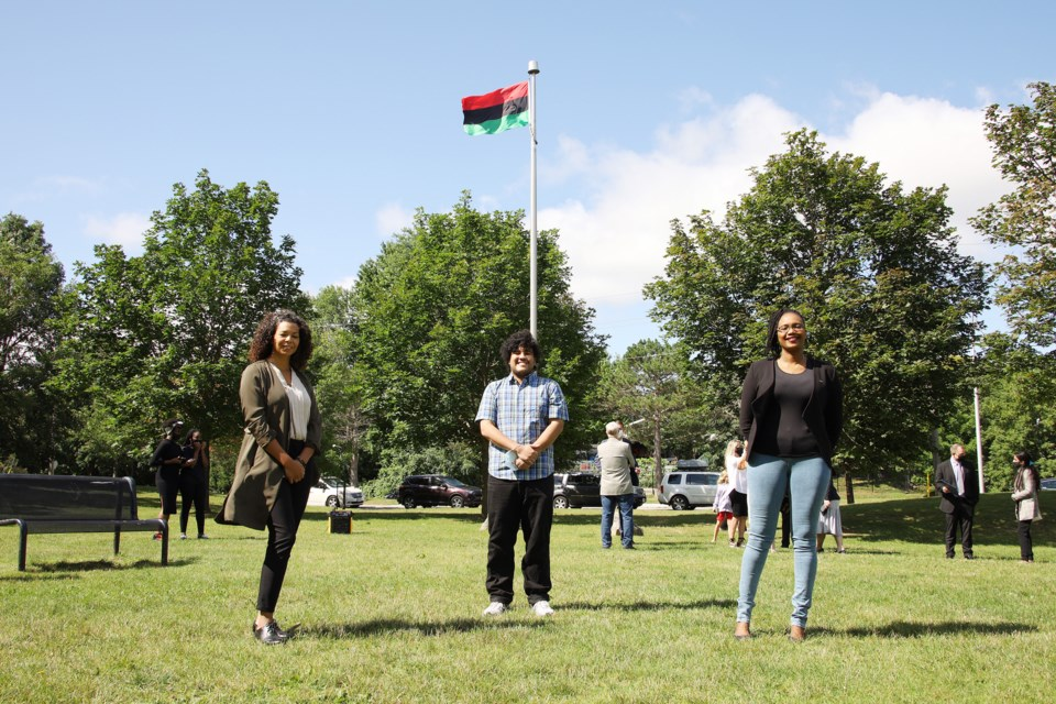 Newmarket African Caribbean Canadian Association (NACCA) treasurer Alicia Katsavos (from left), Matthew Palomino, and NACCA chairperson Jerisha Grant-Hall in front of the Pan-African flag flying over Newmarket's Peace Park July 30.  Greg King for NewmarketToday