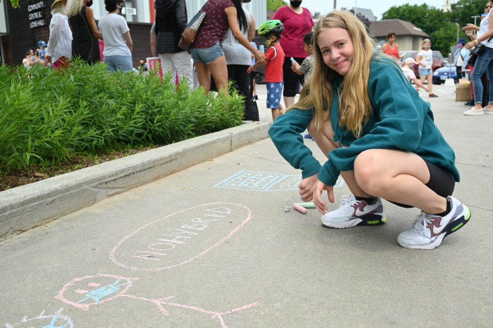 Grade 8 student Grace Lodoen  makes a chalk drawing opposing hybrid learning, at the Riverwalk Commons July 24.