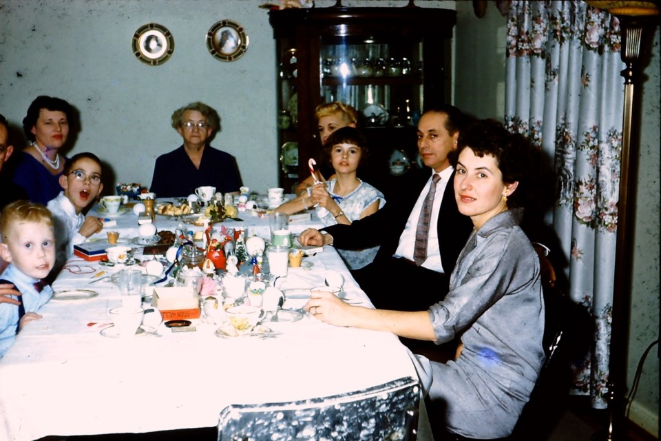 Family gathers for Christmas dinner in the early 1960s.