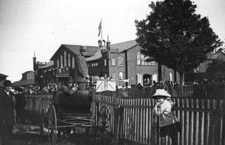 A little girl peers at the camera, with the Palace at Newmarket Fair Grounds behind her.