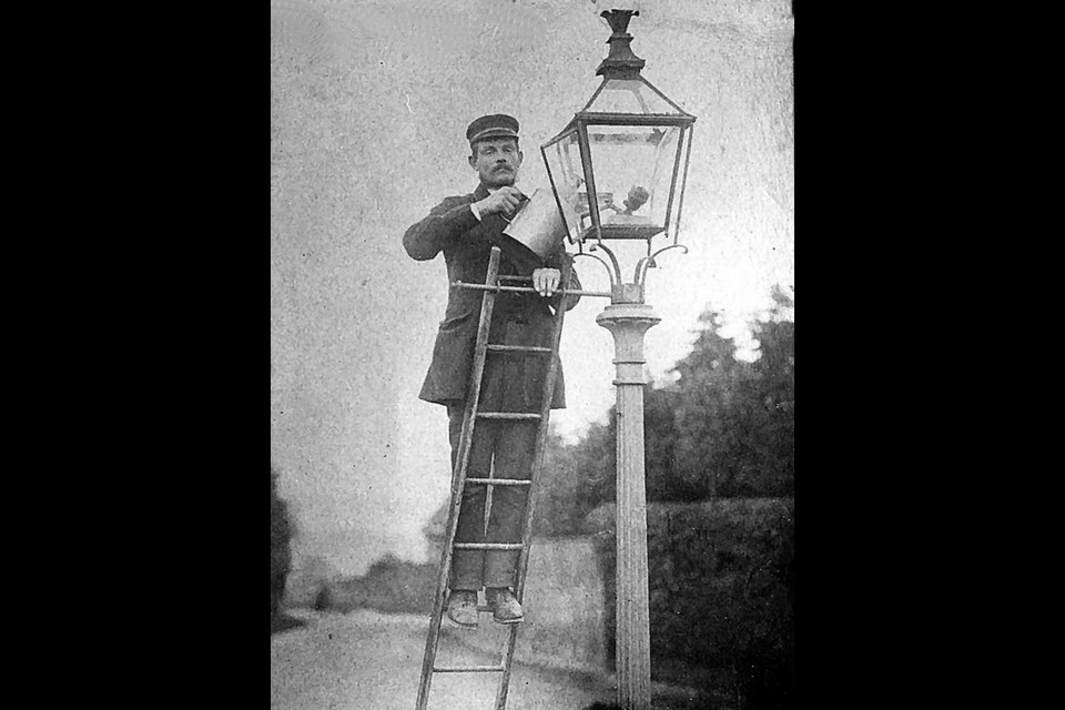 The town lamplighter went about each evening and morning, carrying a little ladder, a cloth for cleaning the lamp and a coal oil can after they were installed on Main Street in 1879.
