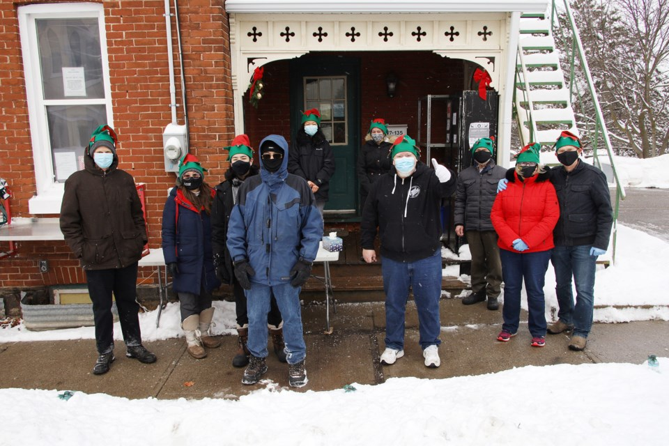 Pastor Andrew Hamilton, here with a thumb's up, and volunteers from the Christian Baptist Church on Newmarket's Main Street expanded their Porch Pantry Mission Dec. 26 by providing 70 free meals and gifts to the town's homeless and anyone in need.  Greg King for NewmarketToday