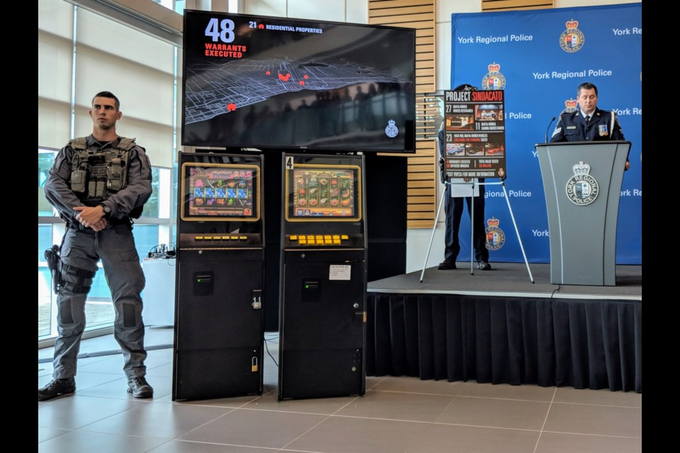 A York Regional Police tactical officer stands beside video gaming machines seized in the Figliomeni crime family bust. Kim Champion/NewmarketToday