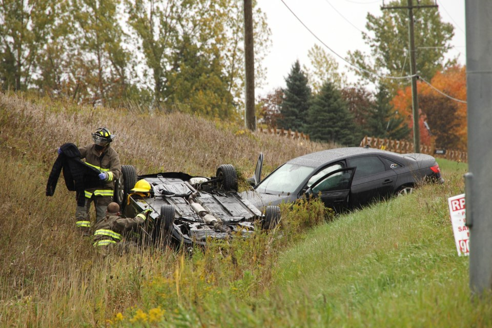 Firefighters determine how to best extract the occupant of the overturned vehicle at the side of Highway 9 and Keele Street Oct. 15.  Greg King for NewmarketToday