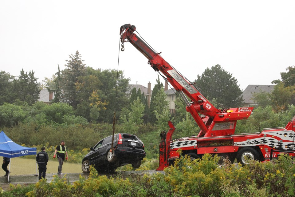 A crane retrieved a vehicle from the bottom of a stormwater management pond in Newmarket this afternoon. Greg King for NewmarketToday