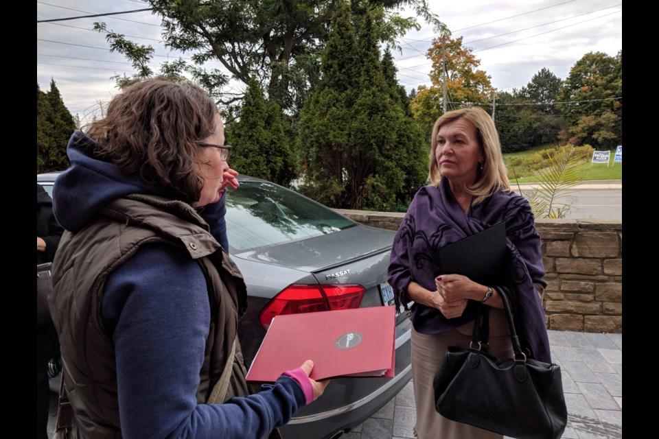 Protestor Jessa McLean asks Newmarket-Aurora MPP Christine Elliott to take their concerns about a fair minimum wage to Queen's Park.