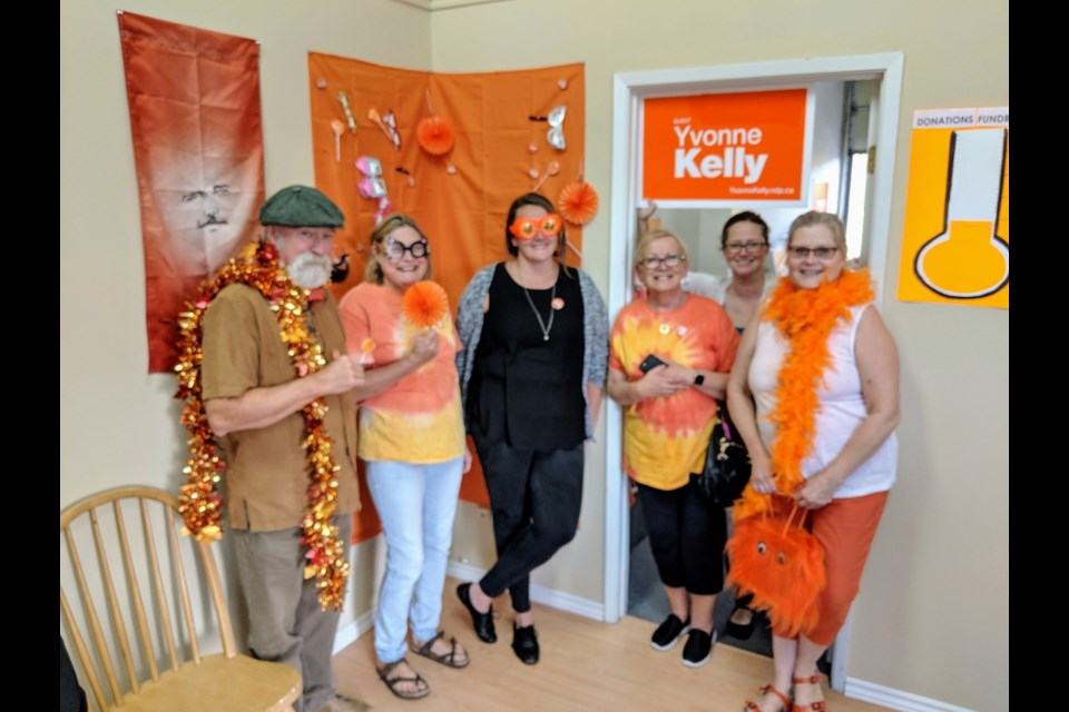 "Newmarket-Aurora federal NDP candidate Yvonne Kelly (far right) officially opened her campaign office on Leslie Street Sept. 12 surrounded by supporters, including husband, Rick Kelly (left), volunteers Chris Loree, Rayanne Lees and Pam Allard, and York-Simcoe NDP candidate Jessa McLean. Visitors can ham it up in the ""orange crush"" photo booth, shown above. Kim Champion/NewmarketToday"