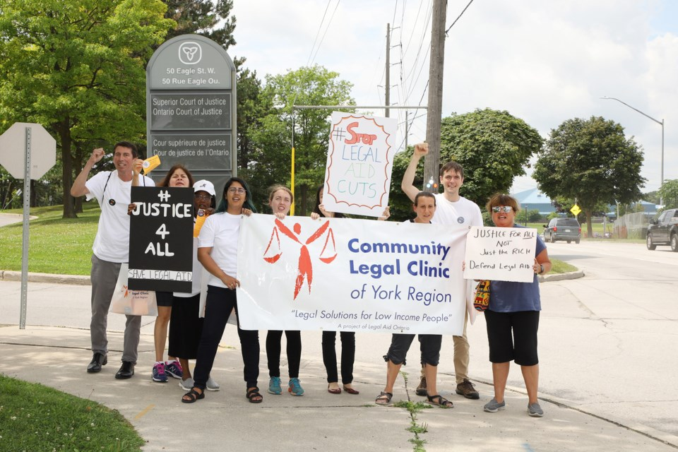Community Legal Clinic of York Region staff marched with their banner at the Eagle Street entrance to the Newmarket courthouse parking lot yesterday.  Greg King for NewmarketToday