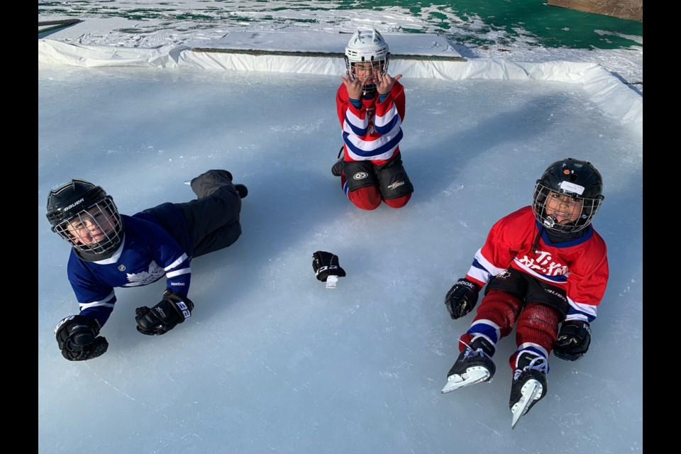 Local children Conor, Arthur and Drake take a break from skating at the volunteer-run Newmarket Lions Park Community Hockey Rink. Supplied photo/Chris Howie