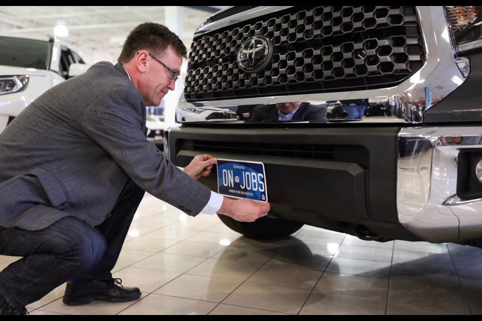 Bill Walker, minister of Government and Consumer Services, places the new commercial licence plate on a truck. Supplied photo/Government of Ontario