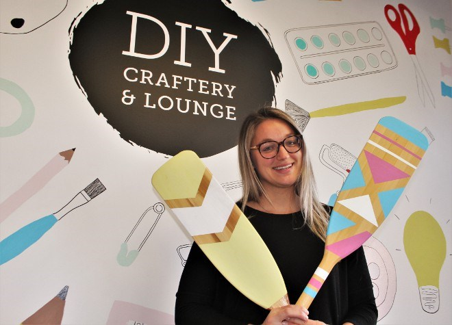 Kelsey Cutinello, owner of DIY Craftery and Lounge in Sudbury, poses with a pair of painted canoe paddles made at the craftery. Those are among many craft projects corporate groups can book to host a teambuilding event. (Karen McKinley photo)