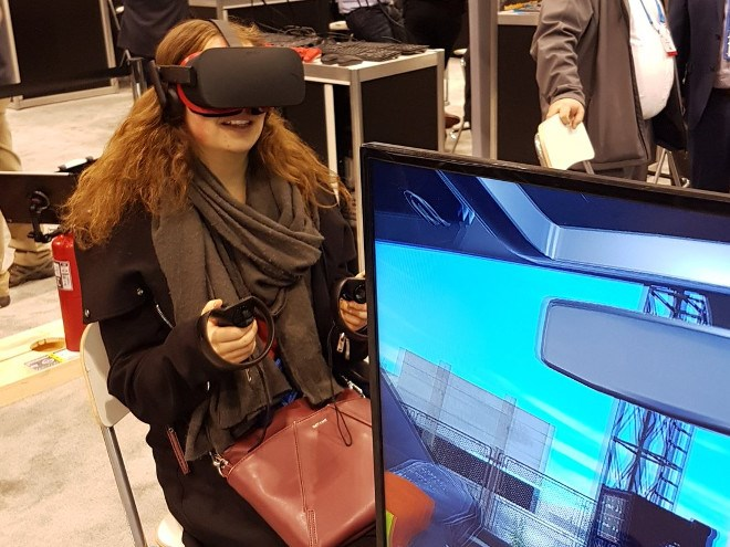 Mining reporter Kelsey Wolfe tries her hand at NORCAT's VR surface mine tour technology at the PDAC mining show in Toronto (Twitter).