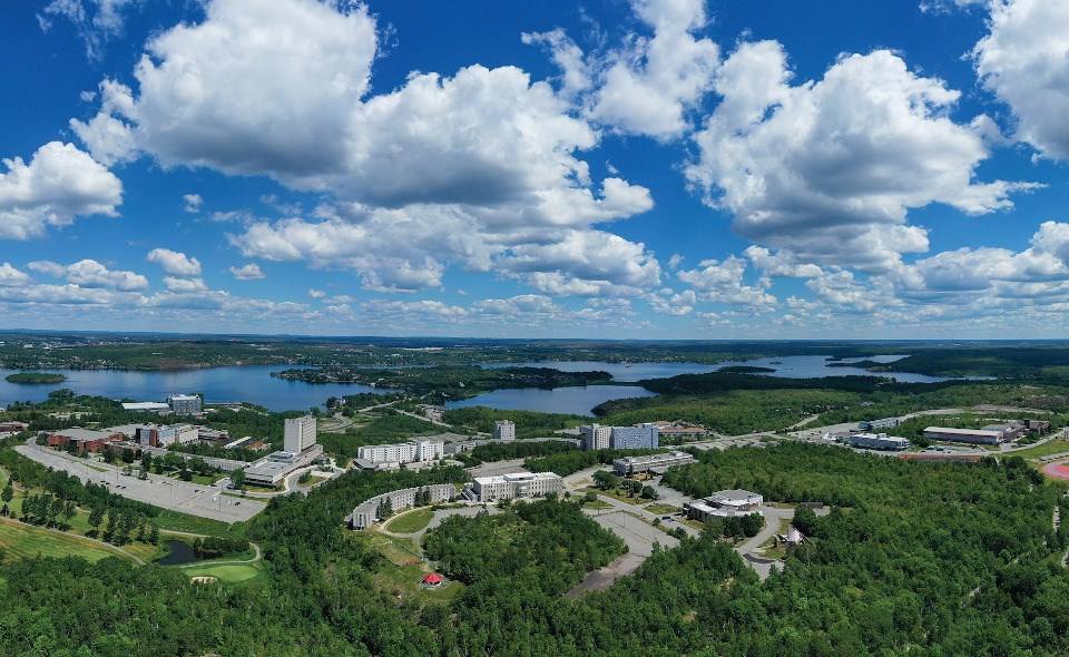 A sea of green surrounds Laurentian University in this aerial image.