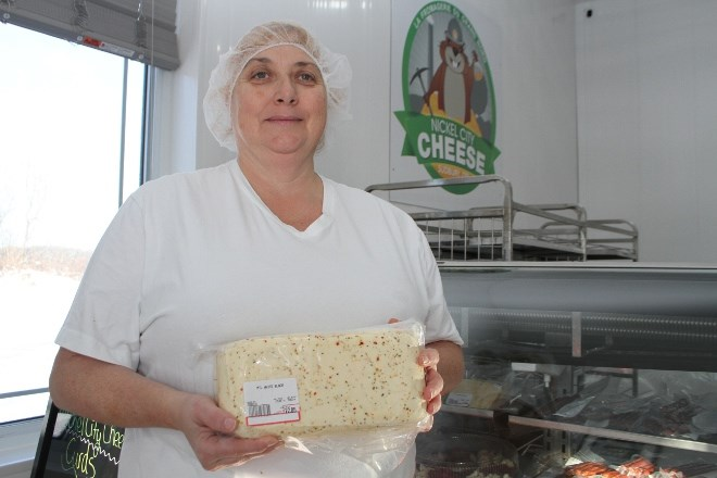 Nicole Paquin show off one of the many cheddar bricks available for sale at Nickel City Cheese at the factory store in Azilda.