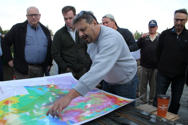 Richard Zamoroz, senior project geologist with New Age Metals, points out locations of core samples while guests examine pieces at the core shack in River Valley before heading to the site. (Karen McKinley photo)
