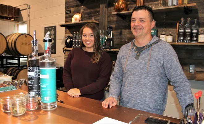 Shane Prodan, owner and proprietor of Crosscut Distillery, and Sarah Del Monte, marketing and events coordinator, show off the triple grain vodka and local harvest gin that are the flagship products, along with some common ingredients and botanicals used in the distilling process.