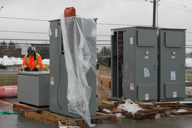 A crew from Steel Control Services worked to install a Tesla SuperCharger in late November. The infrastructure is a Northern Ontario first for the California-based car maker, which is planning to roll out 15 charging stations across the North. (Lindsay Kelly photo)