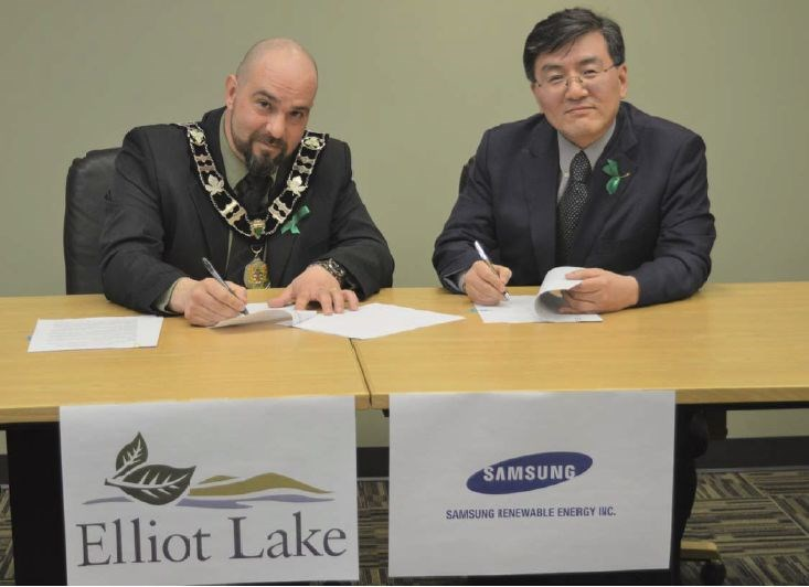 Elliot Lake Mayor Dan Marchisella (left) and Samsung Renewable Energy president Eskay Lee signed a memorandum of understanding on April 11 that will form the basis of an agreement to produce and store renewable energy for the city's facilities. (Submitted photo)
