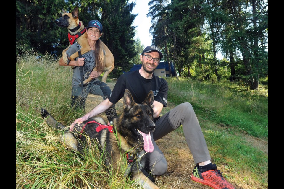 North Shore Rescue volunteers and dog trainers Ellie Lamb and Ryan Morasiewicz proudly show off the team's newest recruits – Dreki, a Belgian Malinois and Neiko, a German shepherd.