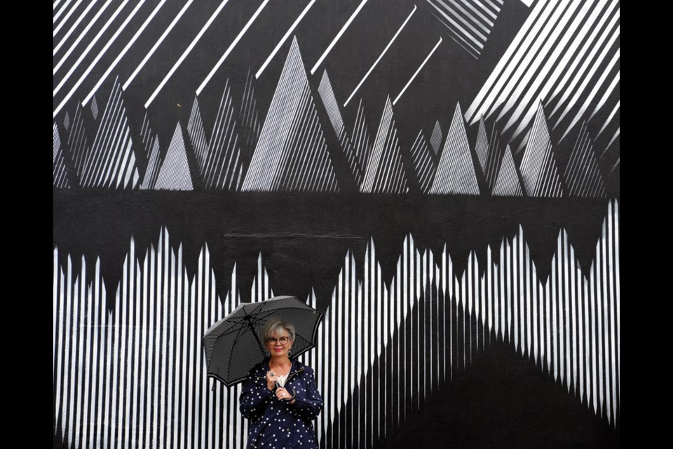 Highland Optical owner Sharyn Webber takes in a striking black and white mural by artist Kari Kristensen in North Vancouver's Edgemont Village, part of the Vancouver Mural Festival running until Aug. 22, 2021.