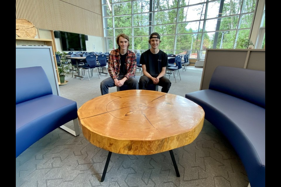 École Argyle Secondary graduates Oscar and Theo Derban sit at the coffee table Oscar crafted from a  fallen 280-year-old fir tree. They hope the table will spark discussions about British Columbia's old-growth forests for years to come in the school's library.
