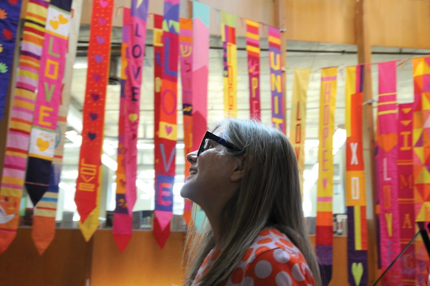 Artist and organizer Berene Campbell stands under a banner of quilts in the stairwell at Lynn Valley library after they were installed on July 19, 2021. The massive community project has been underway for months, following the tragic stabbing event of March 27, 2021.