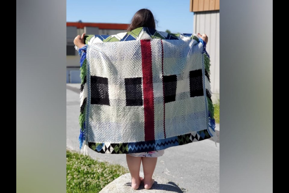 Caitlin Aleck of Tsleil-Waututh Nation displays a robe she has woven for artist Dan Friday's Future Artifacts exhibition at the Museum of Northwest Art.