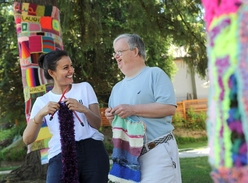 Simran Likhari, community arts projects lead at Cascadia Society, with Knitter William Skuse show off their 'yarn bombing' skills in front of the North Vancouver centre. The summer art project has helped brighten up the street.