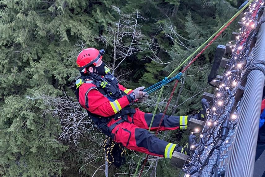 Members of District of North Vancouver Fire and Rescue Services make their way to a couple and their dog stranded near the Capilano Suspension Bridge, Saturday.