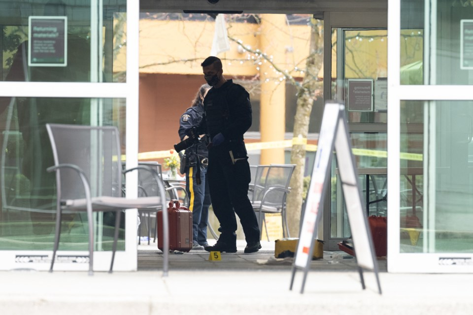 Police officers survey the scene following a stabbing spree at the Lynn Valley library complex on Saturday, March 27, 2021.