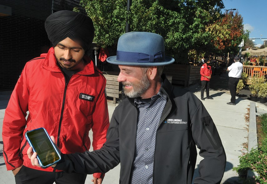 Lower Lonsdale Business Improvement Area executive director Greg Holmes checks out his vaccine status with Rajan Singh of Goldilox Security outside the restaurant strip by the Shipyards, Sept. 13.